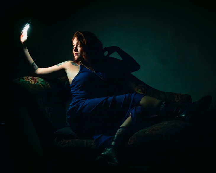 Lisa Friedrich laying on chaise in dark on phone